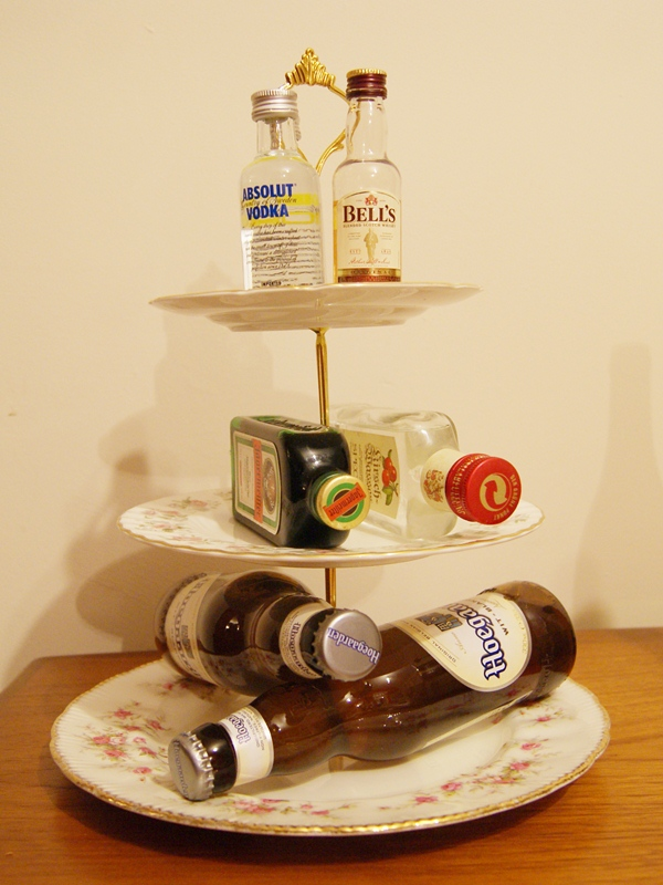 A collection of beers and spirits on a cake stand.