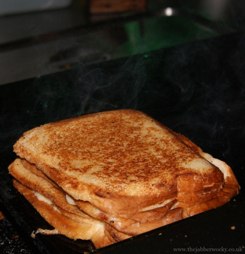 A 3 slice, three layer toastie sizzling on the sandwich presses