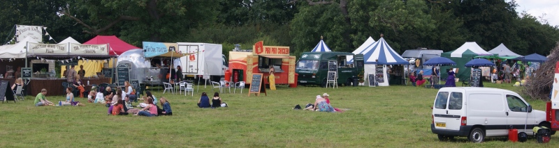 A line of catering vans, trailers, stalls and tents, with tables, chairs and customers in front of them.