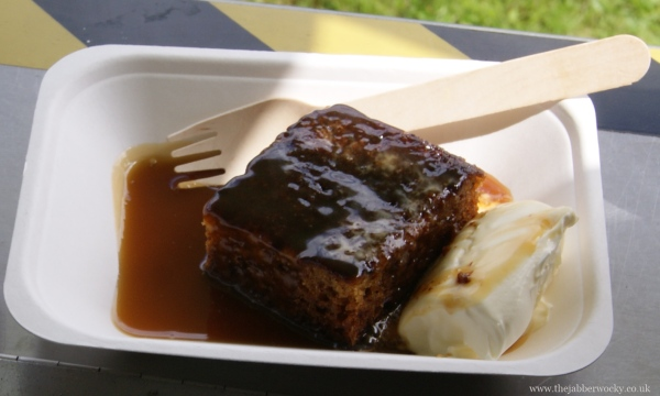A generous chuck of warm sticky toffee pudding topped with toffee sauce and clotted cream