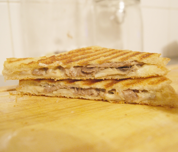 A halved toastie on a chopping board.